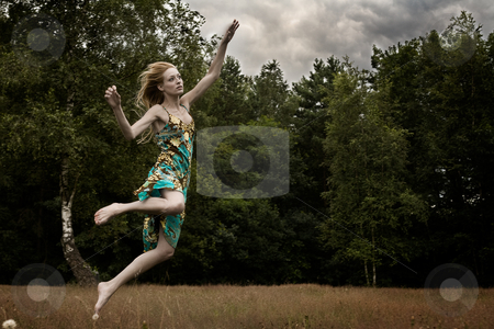 Jumping in the field stock photo, Young blond woman wearing a dress in the forest by Frenk and Danielle Kaufmann