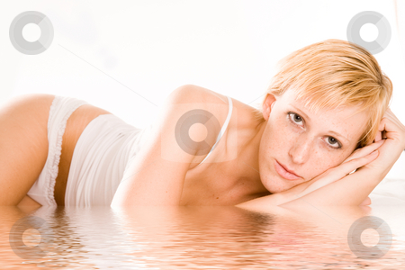 Beautiful blond in lingerie looking at nothing stock photo, Studio portrait of a blond short haired girl in lingerie laying on her bed by Frenk and Danielle Kaufmann