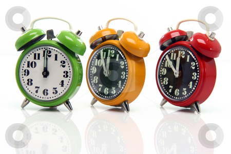 Timing alarm clocks stock photo, Timing red yellow and green alarm clock untill twelve oclock closeup with nice reflection by EVANGELOS THOMAIDIS