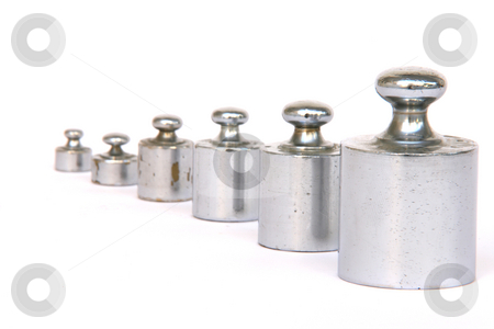 Different weights stock photo, Different weight units in a row focus on the big one isolated on white background by EVANGELOS THOMAIDIS
