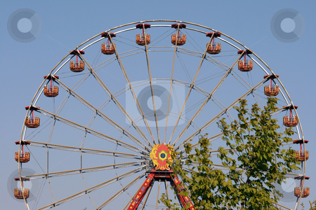 Amusement and tree stock photo, Big spinning wheel behind a tree at amusement park and blue sky background by EVANGELOS THOMAIDIS