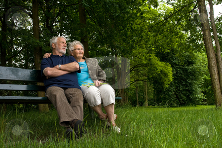 Elderly couple relaxing on a park bench stock photo, Elderly couple enjoying nature on a park bench by Frenk and Danielle Kaufmann