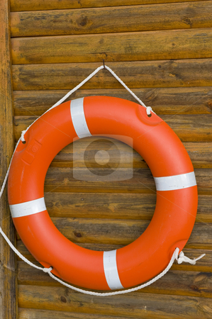 Lifebuoy hanging on a wooden wall stock photo, A bright orange lifebuoy hanging on a wooden wall at a swimming pool. by Nicolaas Traut