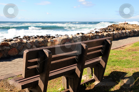 Wooden bench by the sea stock photo, An empty wooden bench next to a pathway that runs next to a rocky shore, on a sunny Winters day. by Nicolaas Traut