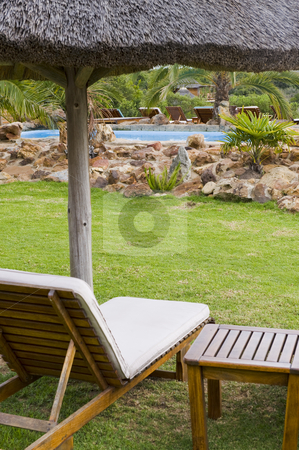 Beautiful garden with swimming pool stock photo, Beautiful lush garden on a farm in the countryside. Some deck-chairs are set on grass near a swimming pool. by Nicolaas Traut