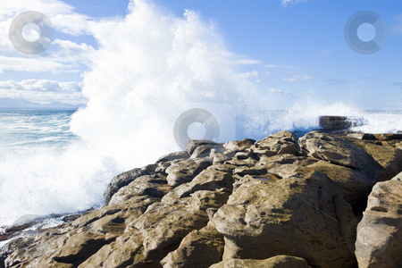 Powerful waves stock photo, Powerful wave hammering a rocky shore resulting in a spectacular spray. by Nicolaas Traut