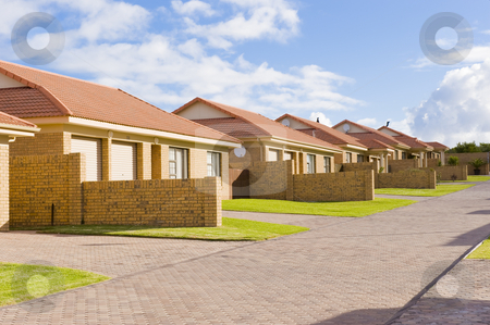 Suburban housing development stock photo, A typical suburban housing development showing a row of similar houses in a compound. by Nicolaas Traut