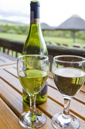 Wine at an outside restaurant stock photo, Glasses of white wine on a wooden table at an outside restaurant on a cloudy day in the countryside. by Nicolaas Traut