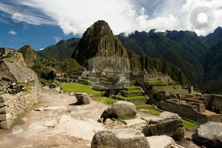 Machu Picchu stock photo, Machu Picchu  is a pre-Columbian Inca site located 2,400 meters (7,875 ft) above sea level. It is situated on a mountain ridge above the Urubamba Valley in Peru, which is 80 km (50 mi) northwest of Cusco. Often referred to as