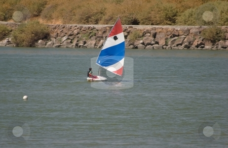 Sailing dinghy stock photo, A dinghy is a type of small boat, often carried or towed by a larger vessel. The term can also refer to small racing yachts or recreational open sailing boats. by Mariusz Jurgielewicz