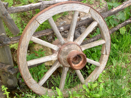 Wagon Wheel stock photo, Wooden Horse Carriage Wheel Leaned on a Fence by Denis Radovanovic