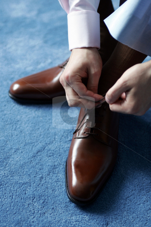 Businessman dressing for work stock photo, Businessman tying his shoes as he gets dressed for work. by Martin Crowdy