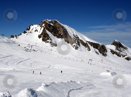 Alpine skiers  stock photo, Skiers on mountainside in Swiss Alps scenery. by Martin Crowdy