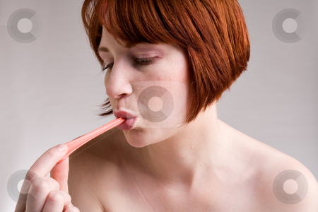 Pull out the bubble gum stock photo, Red haired girl is eating fresh bubblegum by Frenk and Danielle Kaufmann
