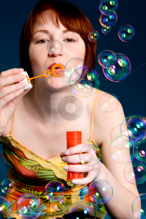 Blowing the bubbles stock photo, Red haired girl is trying to blow some big bubbles by Frenk and Danielle Kaufmann