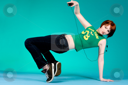 Weird move with mp3 player stock photo, Red haired girl listening to her favourite music by Frenk and Danielle Kaufmann