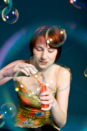 Get some water to blow a bubble stock photo, Red haired girl is trying to blow some big bubbles by Frenk and Danielle Kaufmann