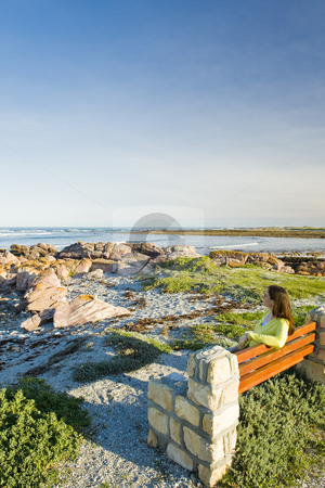 Lady sitting on a bench ovelooking the sea stock photo, A lady sitting by herself on wooden bench looking at the sea. by Nicolaas Traut