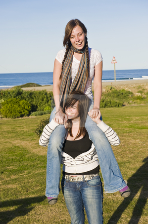 Teenage sisters having fun stock photo, Teenage sisters on vacation, having fun at a coastal town, the ocean visible in the background. by Nicolaas Traut