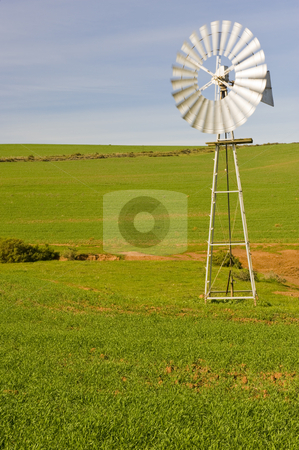 Traditional windmill in a green pasture stock photo, A traditional windmill turning in the wind and pumping water out of the ground into a catchment dam. by Nicolaas Traut