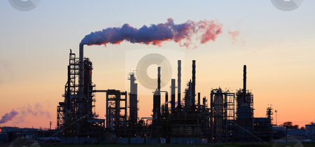 Refinery at Sunset stock photo, Oil refinery at sunset with smoke billowing. by Steve Stedman