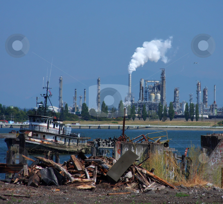 Oil Refinery Across The Bay stock photo, View of an oil refinery from a junked dock area, with trash and vandalism in the foreground. by Steve Stedman