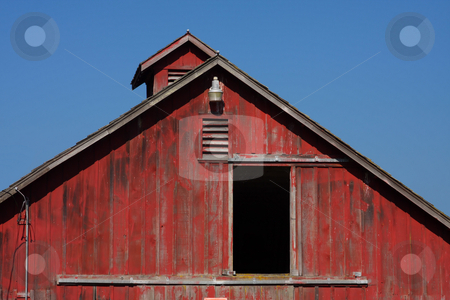 Red Barn stock photo, Door open on a red barn end with blue sky background. by Steve Stedman