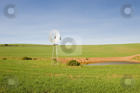Traditional windmill in a green pasture stock photo, A traditional windmill turning in the wind and pumping water out of the ground into a catchment dam to the right. by Nicolaas Traut