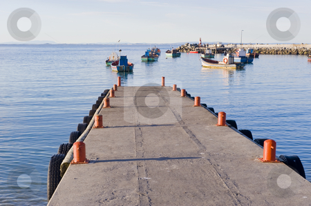 Jetty with fishing boats anchored in the distance stock photo, A jetty in a harbor with some small fishing boats anchored in the distance. by Nicolaas Traut