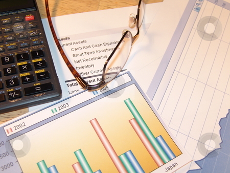 Examining Charts stock photo, Examining financial charts with glasses by Steve Stedman