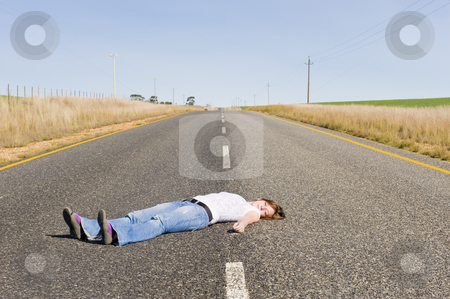 Deserted country-road with girl lying in the middle. stock photo, A deserted country road running through some green fields with a girl lying in the middle of the road playing dead. by Nicolaas Traut