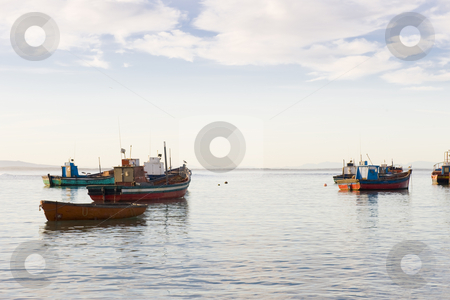 Fishing boats anchored in the harbor stock photo, Small fishing boats anchored in the harbor just before sunset on a quiet afternoon. by Nicolaas Traut