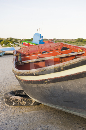 Wooden fishing boat lying on shore stock photo, An old wooden fishing boat lying on the shore, leaning against an old car tyre. by Nicolaas Traut