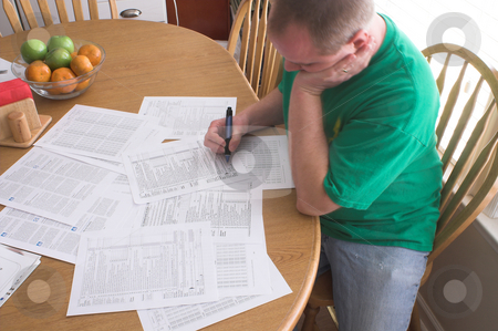 Man Doing Taxes stock photo, A man doing his taxes in the kitchen. by Robert Byron