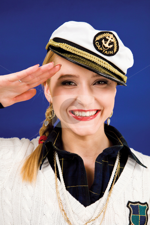 Saluting blond young woman stock photo, Smiling blond young woman saluting in a sea peak-cap by Vitaly Sokolovskiy