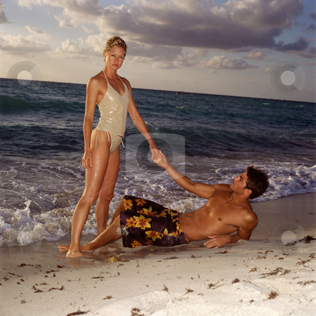 Man and woman on beach stock photo, Couple relaxing on beach by Mpixis World