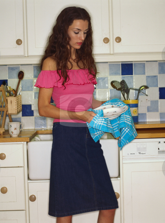 Woman cleaning dishes stock photo, Woman drying plates in kitchen by Mpixis World