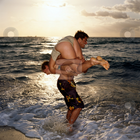 Man carrying woman up at beach stock photo, Couple playing in sea by Mpixis World
