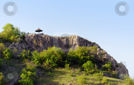 Man under umbrella stock photo, A man under umbrella on the top of a rock by Ivan Paunovic
