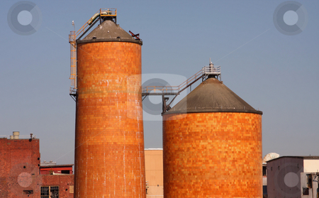 Brick Silos stock photo, Two brick silos from a pulp mill with blue sky background. by Steve Stedman
