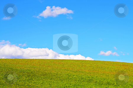 Grass and sky stock photo, A view of a hill covered in grass, with the sky containing a few clouds by Emmanuel Keller