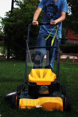 Teenager doing chores stock photo, Teenager mowing the front yard as part of his summer chores. by Patrick Kay