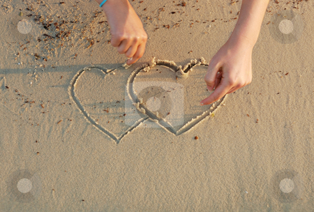Hearts in a sand stock photo, A girl is drawing hearts in a sand by Ivan Paunovic