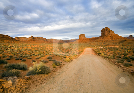 Country Roads stock photo, A dirt road leads through the spectacular scenery of Valley of the Gods in Utah. by Mike Dawson