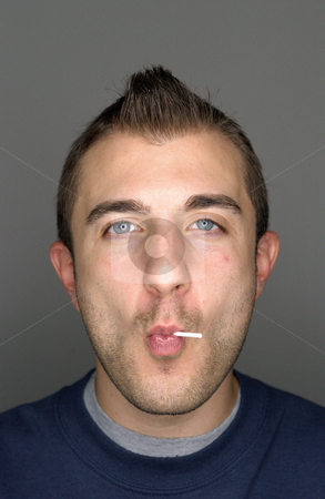 Mohawk man with lollipop stock photo, Man sucking a lollipop by Mpixis World