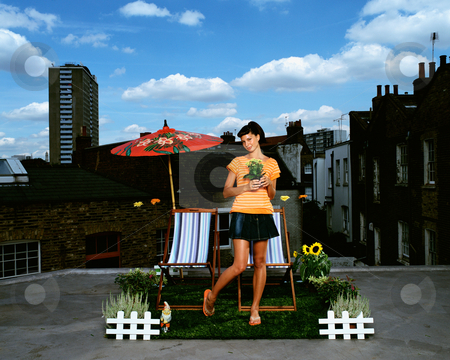 Woman holding flower stock photo, Woman holding flower in roof garden by Mpixis World