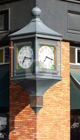 Street Corner Clock stock photo, A large clock on a street corner attached to a brick building. by Steve Stedman