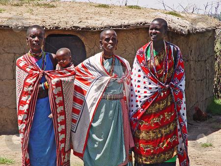 Masai women stock photo, Tree Masai women and a baby posing for the camera. Picture taken at a Masai village in the Masai Mara, Kenya by Emmanuel Keller