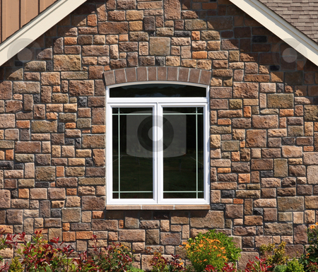 House Stone Wall with Window stock photo, Brick wall with a white framed window with flowers in front. by Steve Stedman