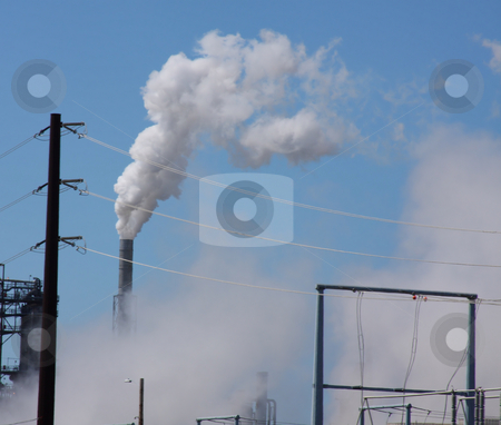 Oil Refinery View stock photo, Oil refinery billowing smoke into blue sky by Steve Stedman
